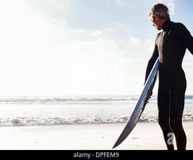 Man at coast with surfboard, Encinitas, California, USA - Stock Photo