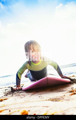 Young girl practicing surfing on beach, Encinitas, California, USA - Stock Photo