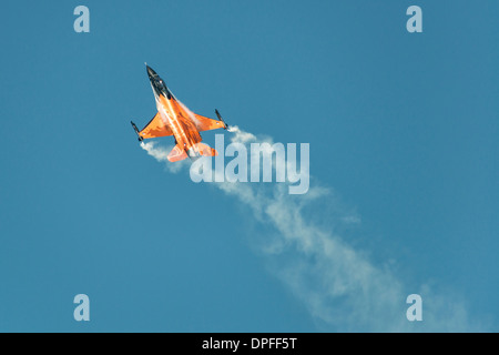 F-16 fighter jet of the Royal Netherlands Air Force demonstration team in it's striking orange livery flies at the - Stock Photo