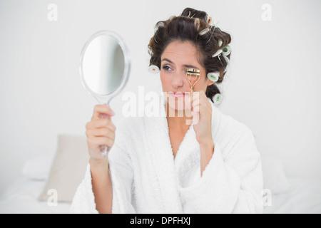 Natural brunette using eyelash curler - Stock Photo