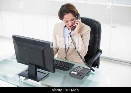 Angry businesswoman shouting into phone - Stock Photo