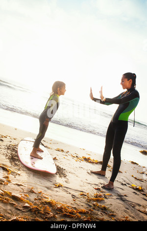 Mother and daughter practicing on surfboard, Encinitas, California, USA - Stock Photo