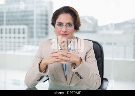 Happy businesswoman sitting at her desk - Stock Photo