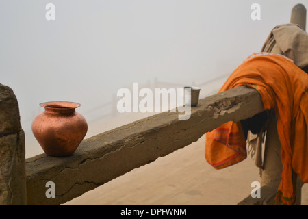 A Hindu Pilgrim is taking a morning bath in the holy river Ganges in Varanasi/Benares on a misty day - Stock Photo