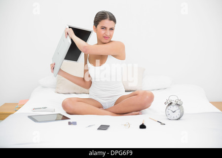 Furious young brown haired model in white pajamas throwing her laptop - Stock Photo