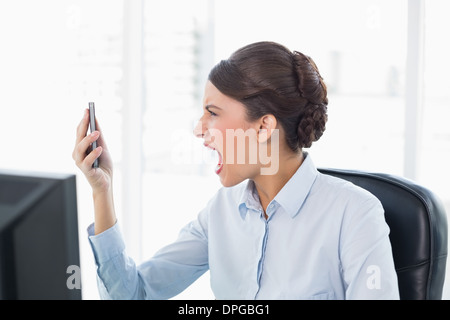 Angry classy brown haired businesswoman shouting at her mobile phone - Stock Photo