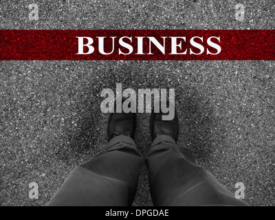 Businessman standing on asphalt starting line with motivation word of Business - Stock Photo