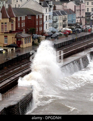 A train is battered by waves as it passes through the Dawlish train station, Devon - Stock Photo