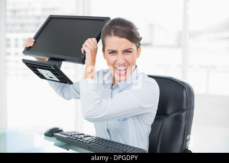 Annoyed classy brown haired businesswoman throwing her computer screen - Stock Photo