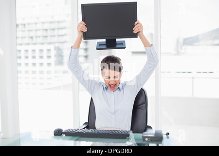 Angry classy brown haired businesswoman throwing her computer screen - Stock Photo