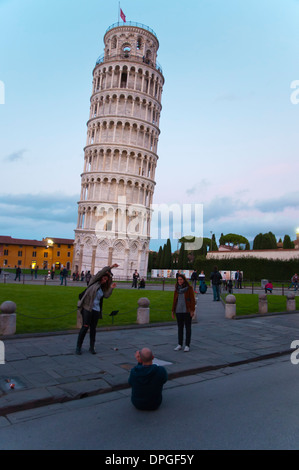 Tourists taking photos and posing in front of Torrre Pendante the leaning tower at Campo dei Miracoli the field - Stock Photo
