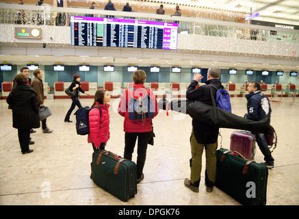 Air passengers checking the departure board, Geneva airport, Switzerland Europe - Stock Photo