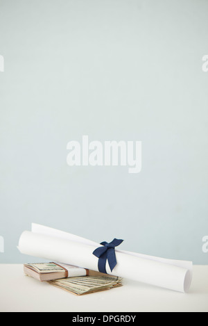 College diploma set atop stacks of cash - Stock Photo
