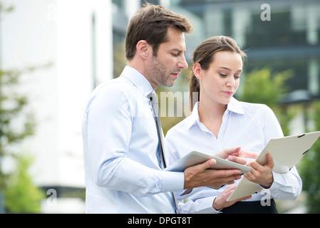 Business associates collaborating using digital tablet - Stock Photo