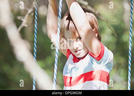 Boy on swing, portrait - Stock Photo