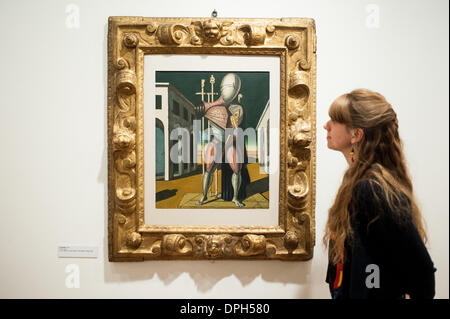 London, UK - 14 January 2014: a member of staff of the Estorick Collection of Modern Italian Art looks at a canvas - Stock Photo
