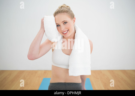 Smiling sporty blonde touching forehead with towel - Stock Photo