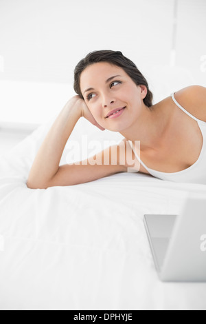 Content casual brunette in white pajamas lying on her bed and looking away - Stock Photo