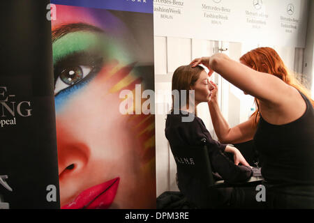 Berlin, Germany. 15th Jan, 2014. A model gets herself prepared backstage during the Autumn/Winter 2014 shows of - Stock Photo