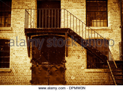 Historic house with bolted door and iron staircase, Liverpool, UK - Stock Photo