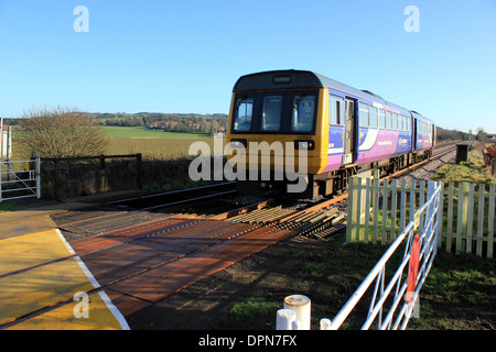 A train owned by Northern rail Pacer no142060 approaches an un-manned level crossing in West Lancashire - Stock Photo