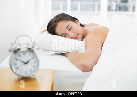 Sleeping woman with blurred alarm clock on bedside table - Stock Photo