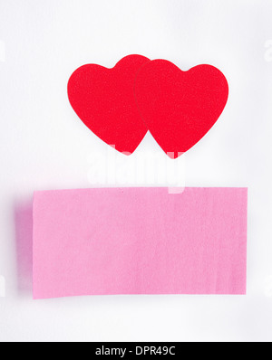 Two red hearts and a sticky-note stuck on paper sheet - Stock Photo