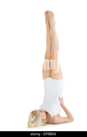 young woman doing a shoulder stand on a yoga mat outdoors