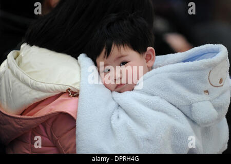 Hangzhou, China's Zhejiang province. 16th Jan, 2014. A 7-month-old baby snuggles up to its mother while waiting - Stock Photo