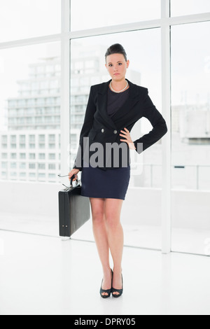 Full length of an elegant businesswoman in suit carrying briefcase in office - Stock Photo