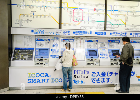 People buying train tickets from a train ticket machine - Stock Photo