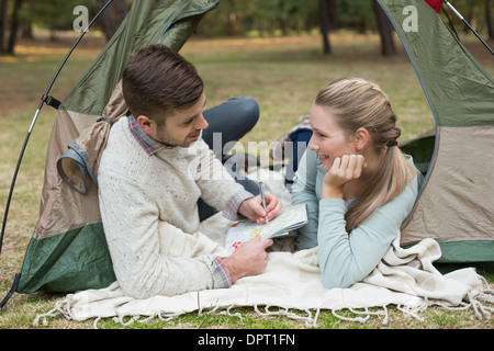 Couple with a map lying in tent - Stock Photo