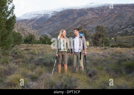 Couple with backpacks and trekking poles against mountain - Stock Photo