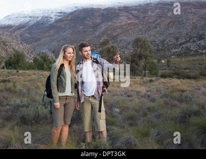 Fit young couple with backpacks on landscape - Stock Photo
