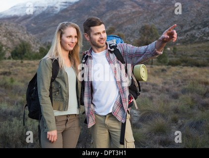 Couple with backpacks standing on landscape - Stock Photo