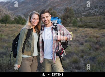 Couple with backpacks standing on forest landscape - Stock Photo