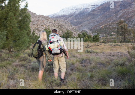 Couple with backpacks walking on forest landscape - Stock Photo