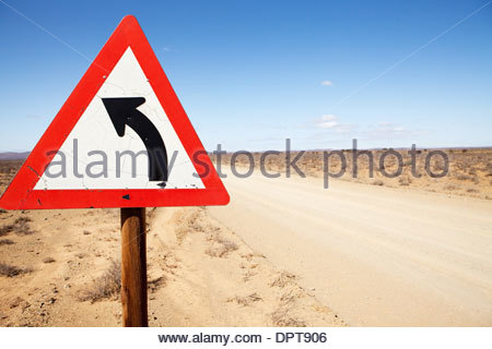 Triangular road warning sign indicating road is turning left - Stock Photo