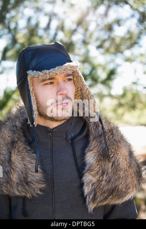Young man in warm clothing looks to his side in forest - Stock Photo
