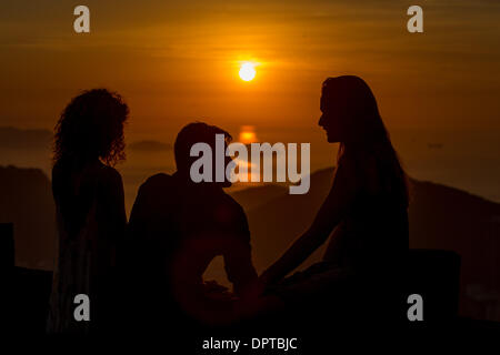 Rio De Janeiro, Brazil. 16th Jan, 2014. Tourists are silhouetted as they watch the sunrise near the Guanabara Bay - Stock Photo