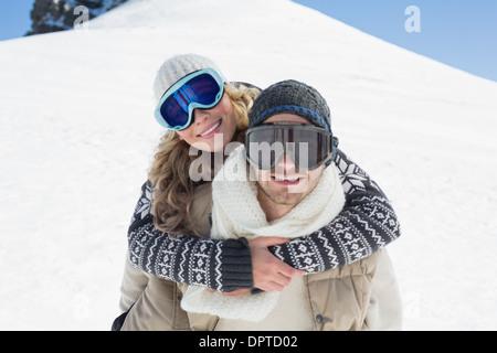 Man piggybacking woman in ski goggles against snow - Stock Photo