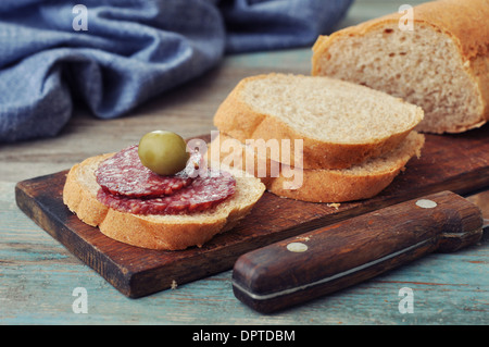 Sliced baguette on wooden cutting board with salami closeup - Stock Photo