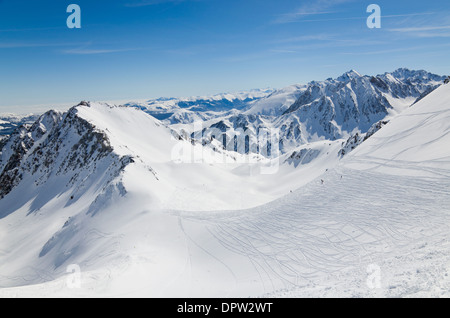 Sunlit downhills with skiers sliding down are photographed against the snow-covered mountain range in the Pyrenees. - Stock Photo