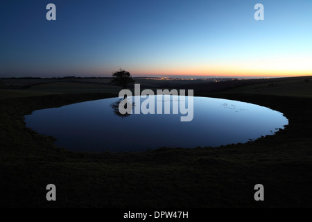 Dew pond on the South Downs at dusk. The sea and the lights of Brighton are just visible in the background. - Stock Photo