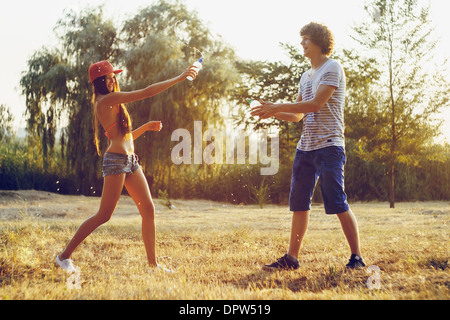 Boy and girl splashing bottled water during summer fun in the park - Stock Photo