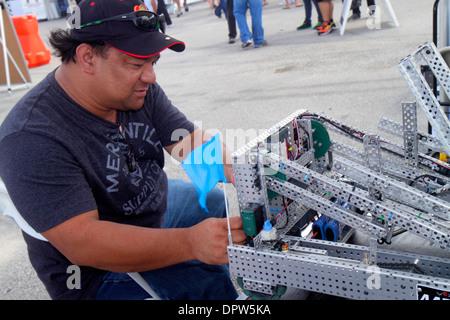 Miami Homestead Florida Speedway DARPA Robotics Challenge Trials remote controlled robot robots Hispanic man repairing - Stock Photo