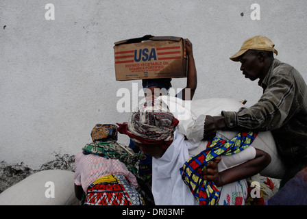 A woman carrying a box of refined vegetable oil donated by USAID agency at World Food Programme WFP distribution - Stock Photo
