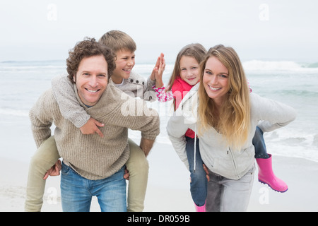 Happy couple piggybacking kids at beach - Stock Photo