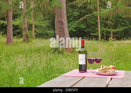 Alfresco dining with a bottle of wine, two glasses and sandwiches on a picnic table in woodland setting. - Stock Photo