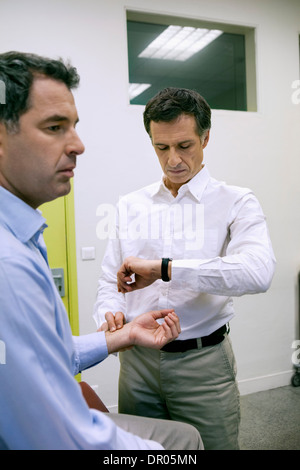 TAKING A MAN'S PULSE - Stock Photo